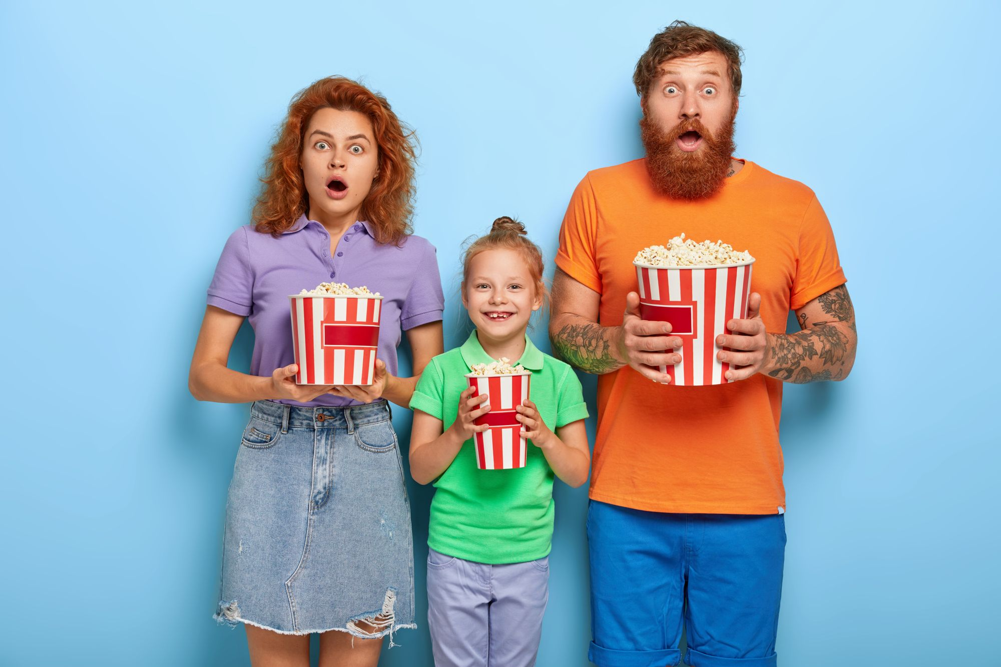 Three family members enjoy watching television at home, mother and father stare with frightened expressions at screen, their small daughter stands between and smiles, eating popcorn.