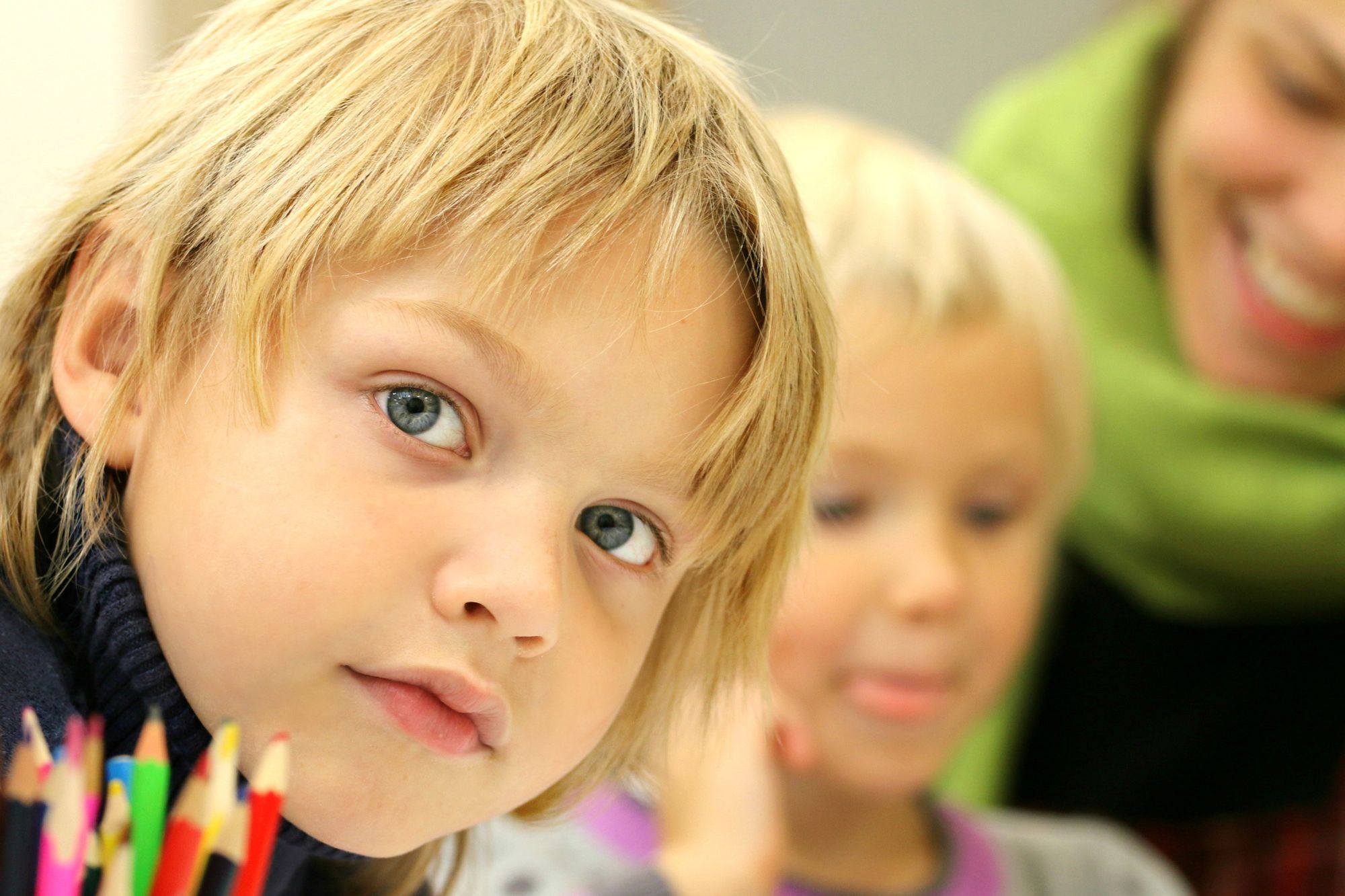 Caucasian boy in school setting near coloring pencils and another child.