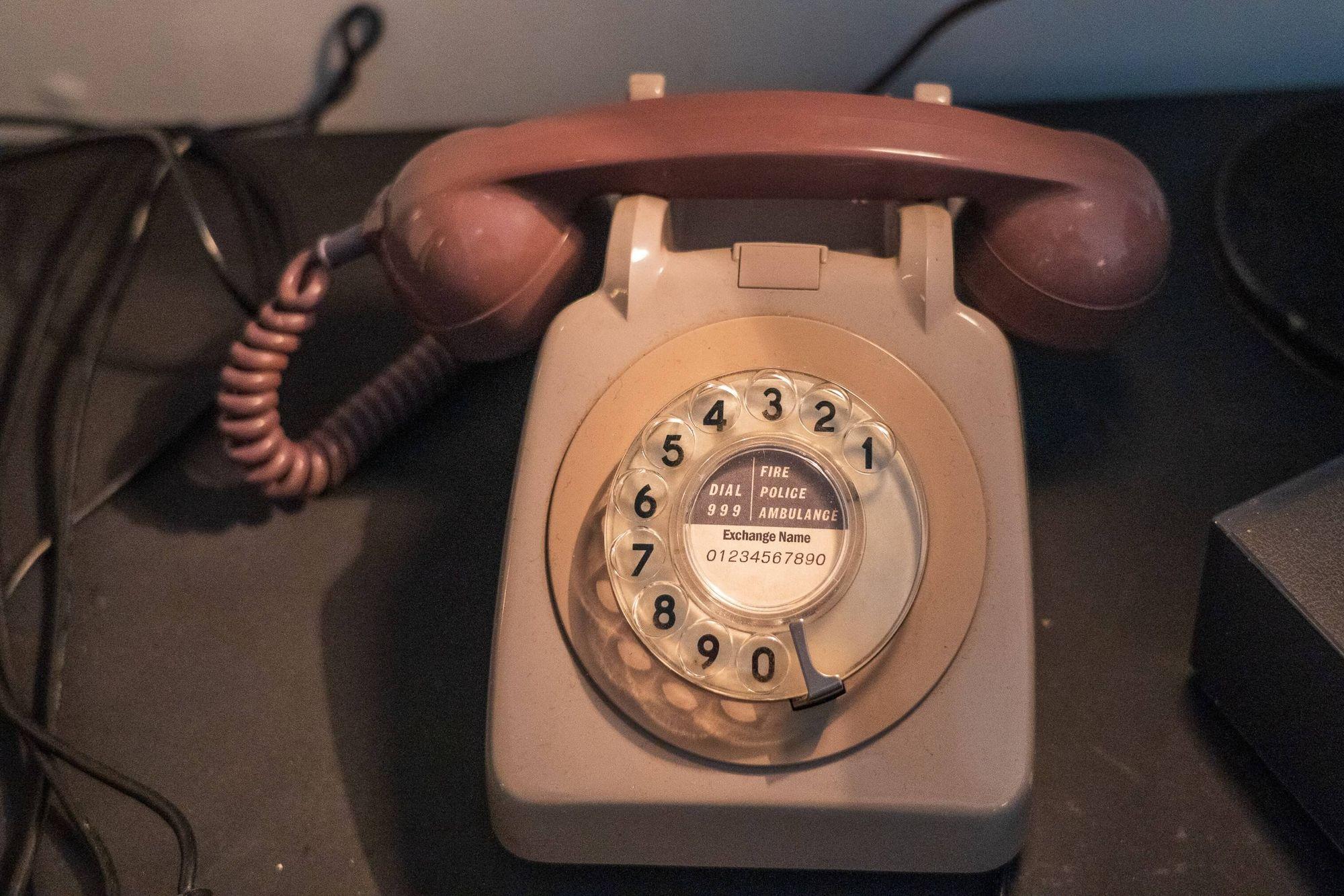 A beige corded rotary phone