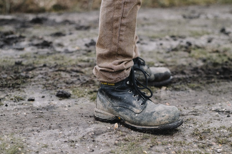 A muddy pair of black work boots worn with brown trousers by an unknown person in a dirty field